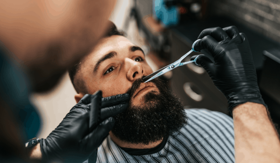 barber trimming a clients beard