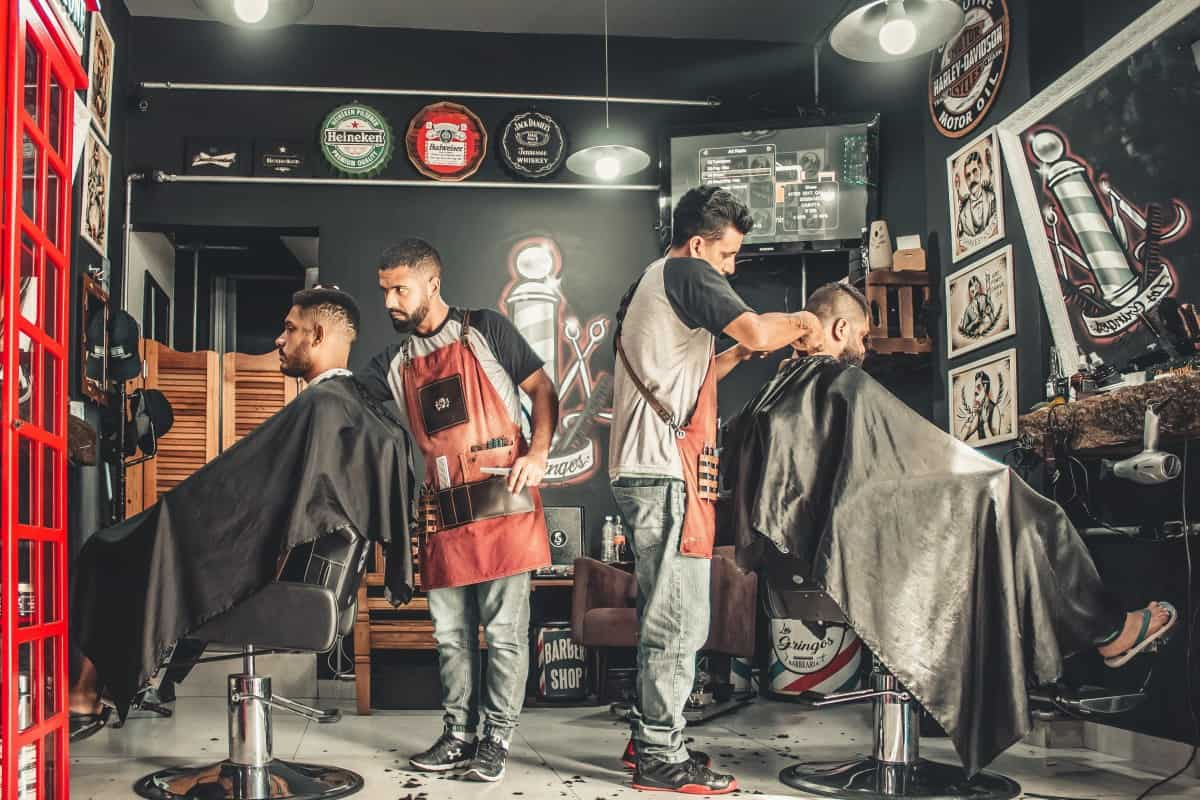 two professional barbers dressed in vintage clothing cutting hair next to each other