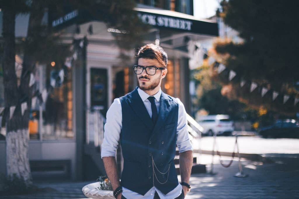 barber standing on a street with a professional outfit and vest