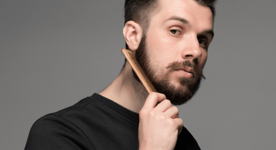 man styling his beard with a comb
