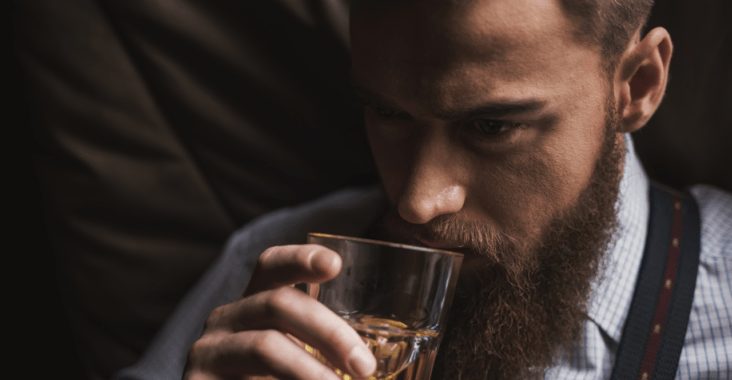man with thick beard drinking out of a cup
