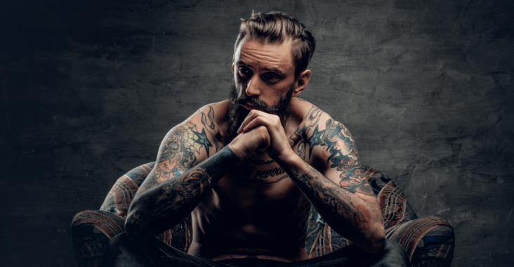 man with tattoos sitting on a couch