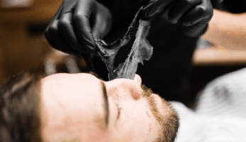 Barbering using a black mask peel on a client