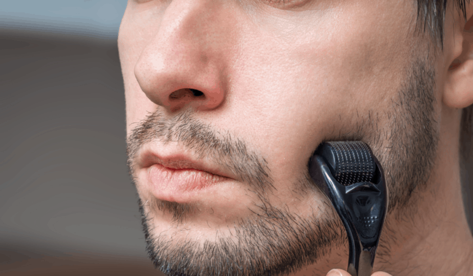 man using a beard roller on his face
