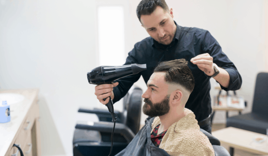 barber blowing drying hair with round brush