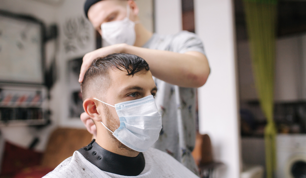 image of a barber cutting hair at the barbershop