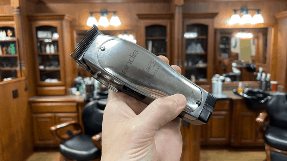 barber holding up andis cordless fade master clipper