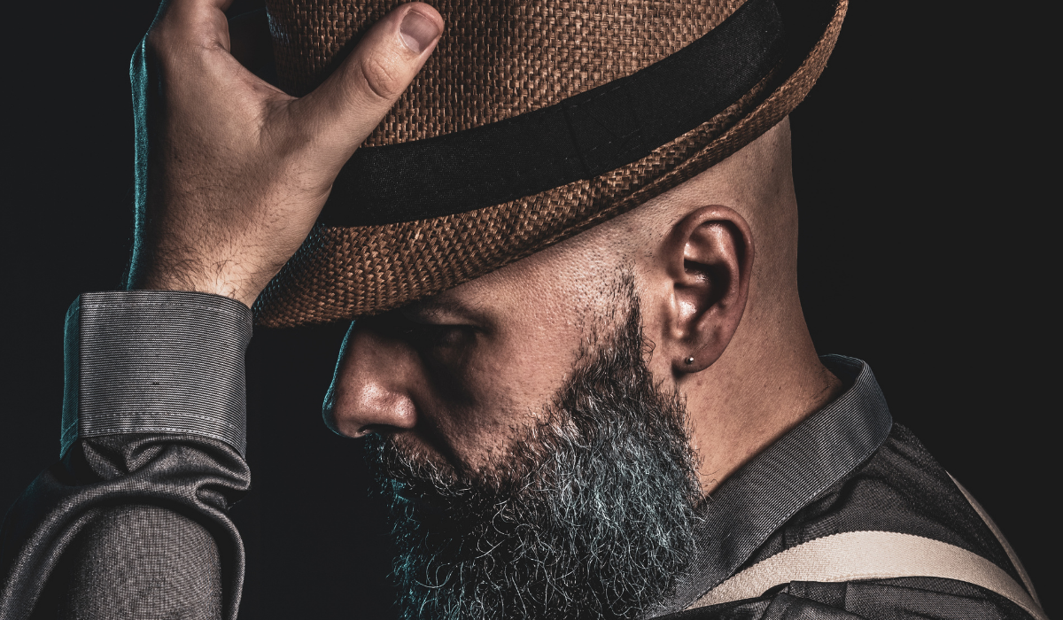Man putting on hat after a haircut
