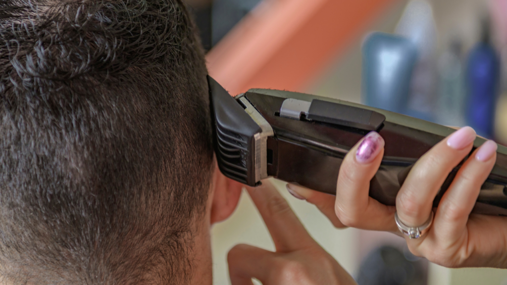 image of a barber cutting hair short around the sides and back of the head