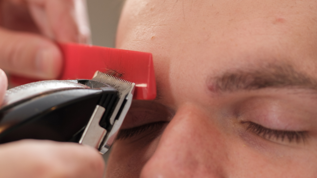 image of a barber using a clipper and comb