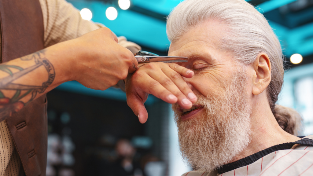 image of a barber using shears to trim eyebrows
