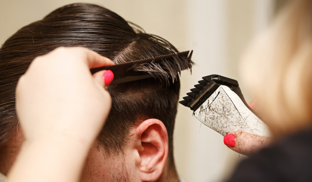 image of a man getting his haircut using a flat top comb and clippers.