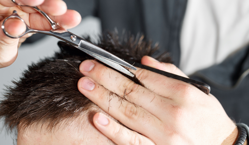image of a man getting the top of his hair cut